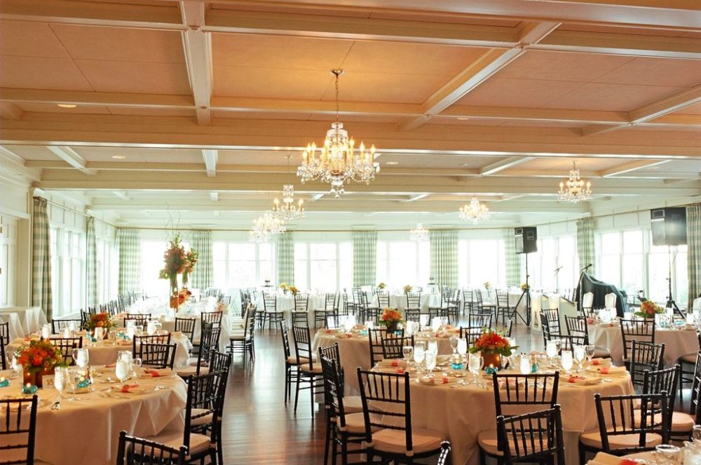 Decorated reception tables in an upscale room with chandeliers